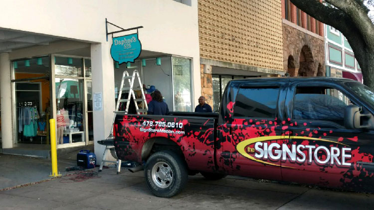 Sign store truck on location in downtown macon installing a sign