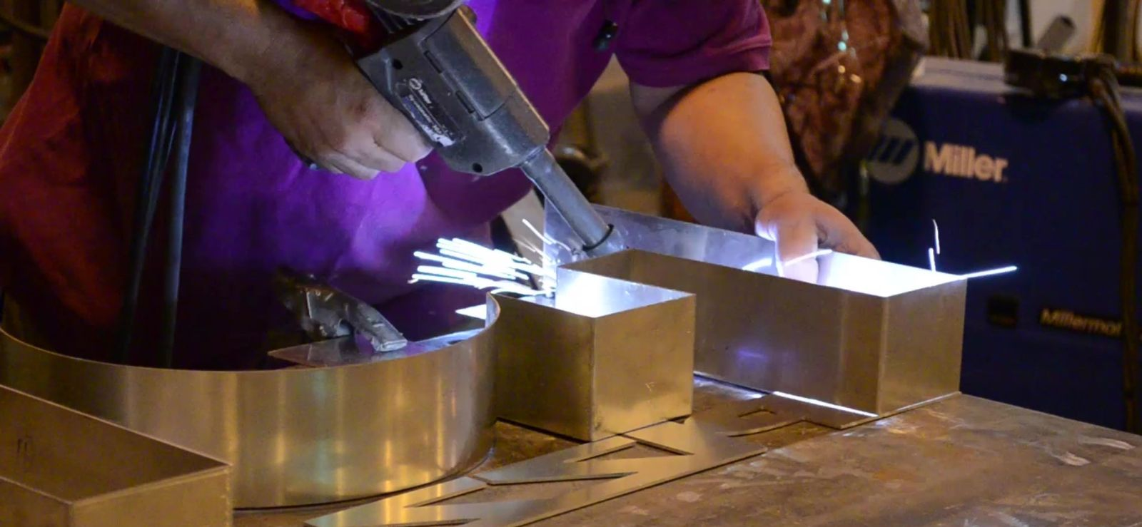 Female Fabricator Constructing Metal Sign Using Specialized Tools